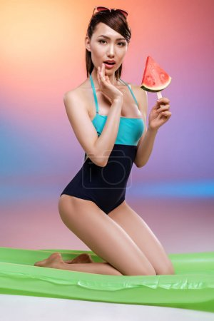 Photo for Sensual asian girl in swimsuit kneeling on swimming mattress and holding watermelon slice on stick - Royalty Free Image
