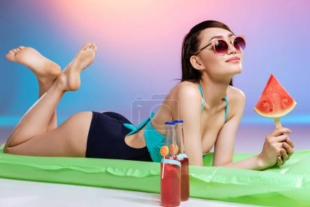 woman in sunglasses relaxing on swimming mattress