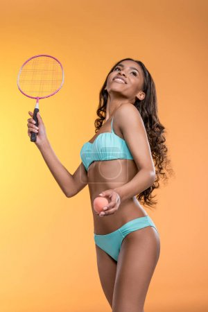 Girl in swimwear playing tennis