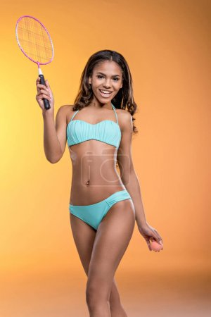 Girl in swimsuit posing with tennis equipment