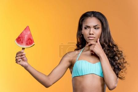 pensive girl holding watermelon piece