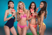 women in swimsuits posing with watermelon slices