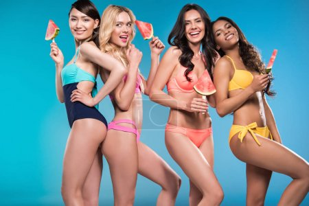 Women in swimsuits posing with watermelon pieces