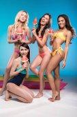 women in swimwear holding watermelon pieces