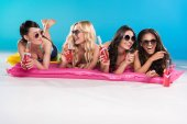 friends in sunglasses lying on swimming mattresses