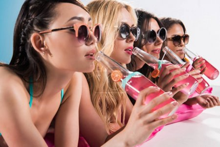 girls drinking cocktails while sunbathing