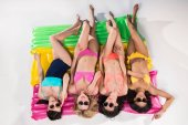 Girls in swimsuits sunbathing on swimming mattresses
