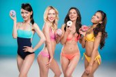 Multiethnic girls in swimsuits holding doughnuts