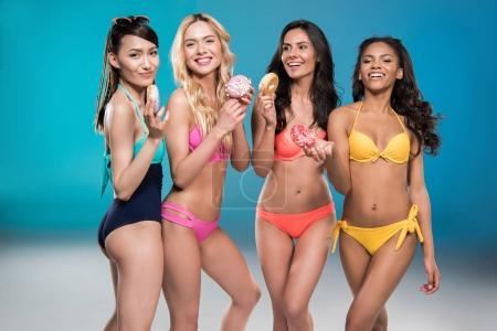 Photo for Young smiling multiethnic girls in swimsuits holding sweet doughnuts - Royalty Free Image
