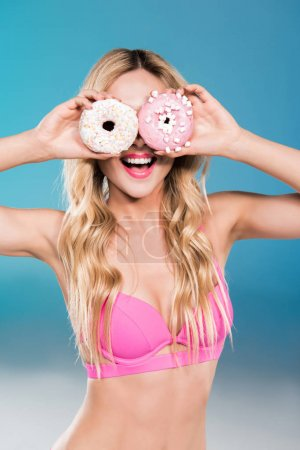 girl in swimsuit holding doughnuts