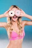 Girl in swimsuit holding doughnuts