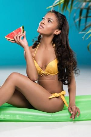 young woman in swimsuit holding watermelon