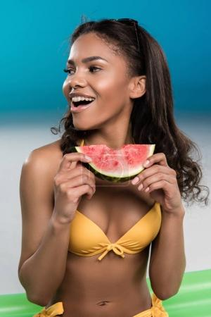 young woman in swimsuit eating watermelon