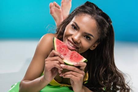 Foto de Afroamericana chica en traje de baño comer sandía mientras está acostado en colchón de natación - Imagen libre de derechos