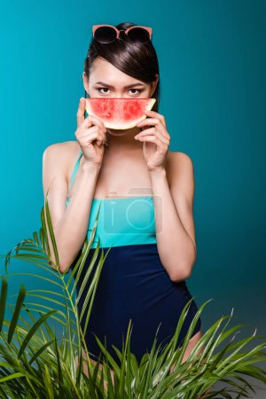 Photo for Portrait of young asian woman in swimsuit holding watermelon piece in front of face - Royalty Free Image