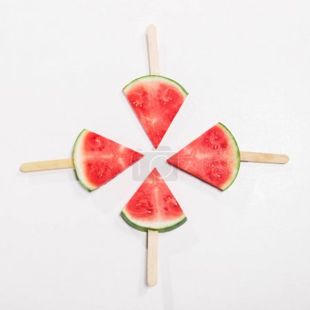 Photo for Top view of ripe watermelon slices on wooden popsicle sticks - Royalty Free Image