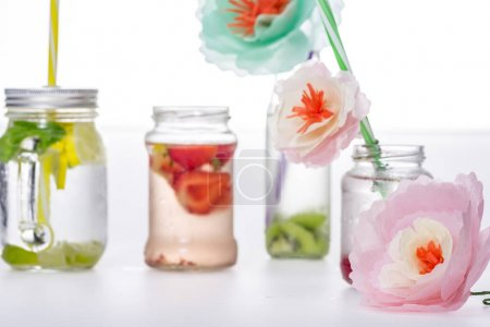 Photo for Refreshing fruity drinks and handmade flowers isolated on white - Royalty Free Image