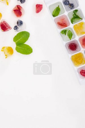 Photo for Top view of ice cubes with berries and fruits isolated on white - Royalty Free Image
