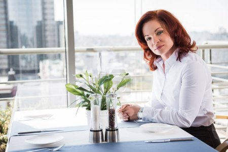 Photo for Beautiful mature businesswoman in restaurant looking at camera - Royalty Free Image