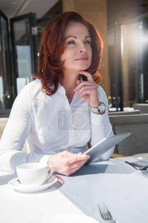 Photo for Thoughtful mature businesswoman with tablet in restaurant - Royalty Free Image