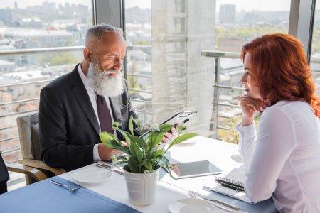 Photo pour Beau homme d'affaires mature regardant contrat donné par partenaire féminin - image libre de droit