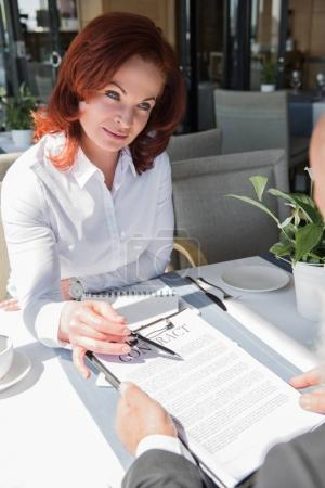 businesswoman presenting contract to partner