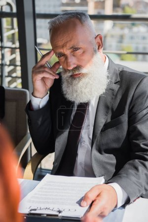 Concentrated mature businessman with contract