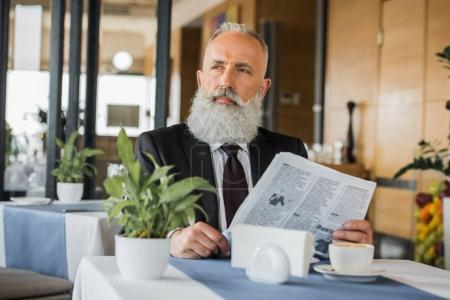 thoughtful businessman with newspaper