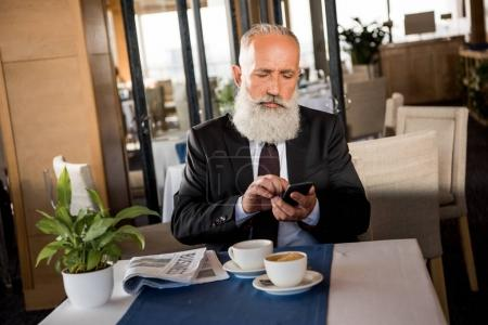 Photo for Handsome bearded businessman using smartphone in restaurant while waiting for meeting - Royalty Free Image