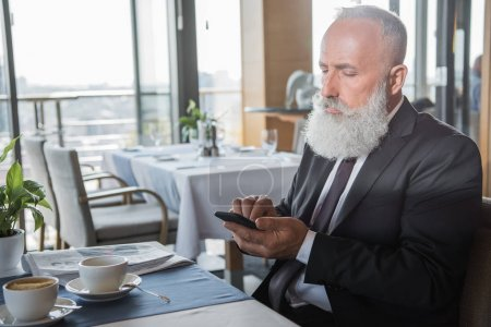 businessman using smartphone in restaurant