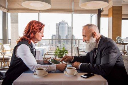 Photo pour Collègues d'affaires matures ayant une réunion au restaurant et regardant tablette - image libre de droit