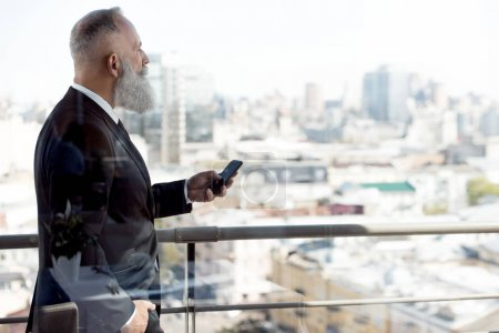 businessman using smartphone on balcony