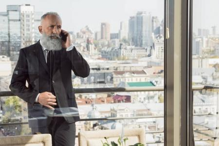 Businessman talking by phone on balcony