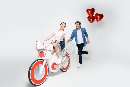 Photo for Girlfriend riding handmade electric bike while her boyfriend running for her with balloons, isolated on grey - Royalty Free Image