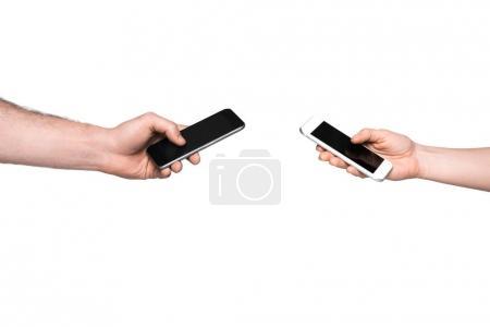 Photo pour Vue recadrée de l'homme et la femme à l'aide de smartphones, isolé sur blanc - image libre de droit