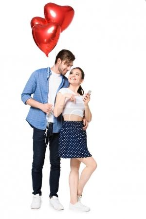 Photo for Young happy couple with heart shaped balloons and smartphone, isolated on white - Royalty Free Image