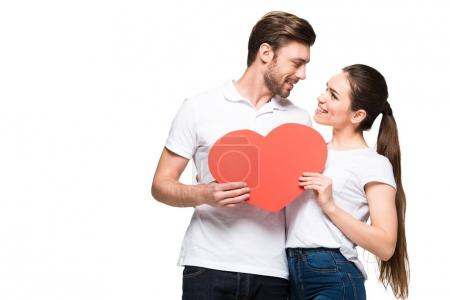Photo for Smiling couple hugging and holding red heart, isolated on white - Royalty Free Image