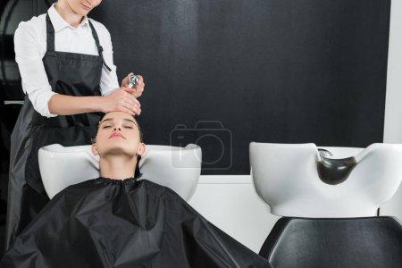 Photo pour Jeune femme ayant lavage de cheveux dans le salon de beauté - image libre de droit