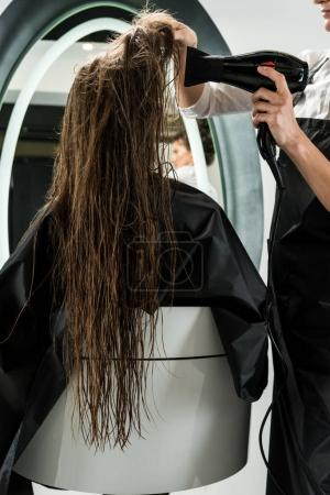 hairdresser drying hair of woman