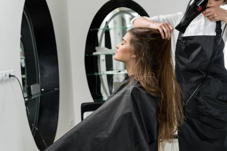 Photo pour Coiffeur séchage des cheveux de jeune femme attrayante dans le salon de beauté - image libre de droit