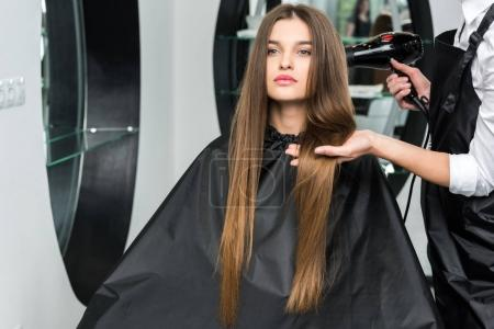 Foto de Seque el cabello brillante de mujer joven en el salón de belleza peluquería - Imagen libre de derechos