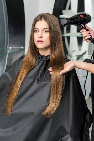 Photo pour Coiffeur séchage cheveux longs de la jeune femme dans le salon de beauté - image libre de droit