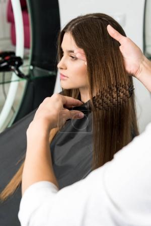 Photo pour Coiffeur brossage cheveux de belle femme dans le salon de beauté - image libre de droit