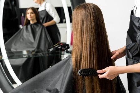 Photo pour Coiffeur brossant les cheveux de la femme dans le salon de beauté - image libre de droit