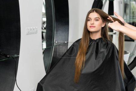 Photo pour Coiffeur brossage cheveux de jeune femme heureuse dans le salon de beauté - image libre de droit