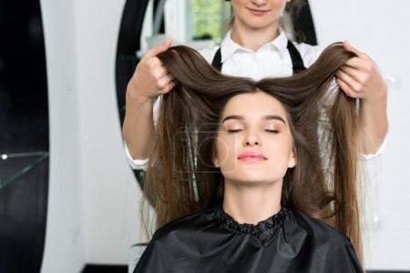 Photo pour Heureuse jeune femme avec de beaux cheveux dans le salon de coiffure - image libre de droit