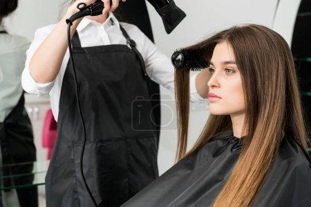 Photo pour Coiffeur séchage des cheveux de jeune belle femme dans le salon de beauté - image libre de droit