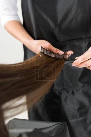 Hairdresser brushing long hair