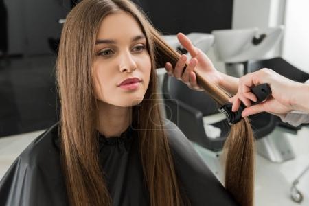 Photo pour Coiffeur brossant les cheveux de la jeune femme dans le salon de beauté - image libre de droit