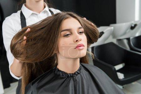 Photo pour Attrayant jeune femme avec de beaux cheveux dans le salon de coiffure - image libre de droit